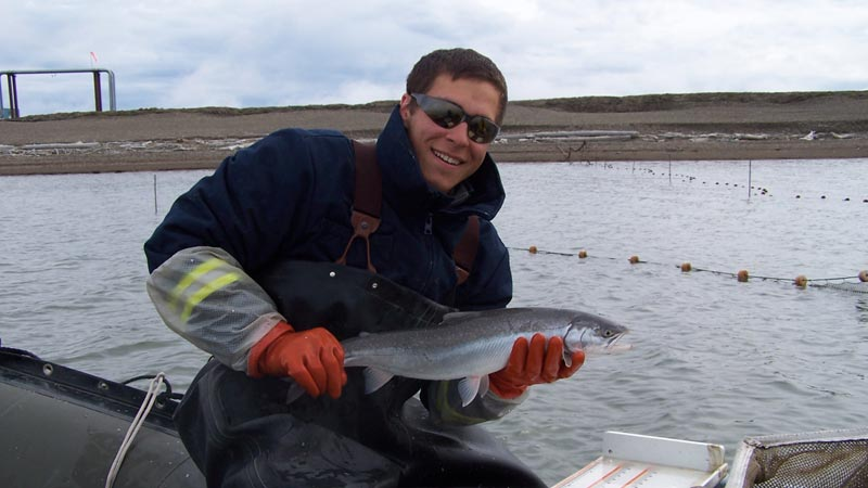 environmental science graduate student holding a fish