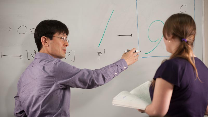 A math instructor explaining a problem to a graduate student