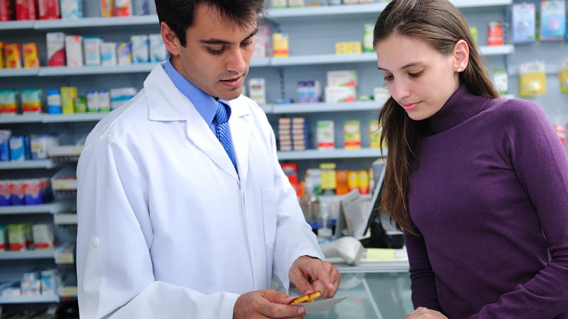 A pharmacists consulting with a patient about the use of the prescription medicine.
