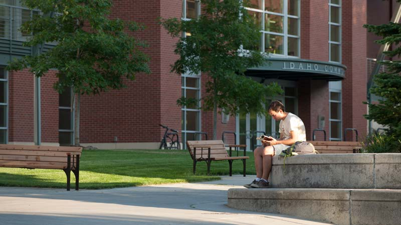 A philosophy student studies outside the University of Idaho's library building.