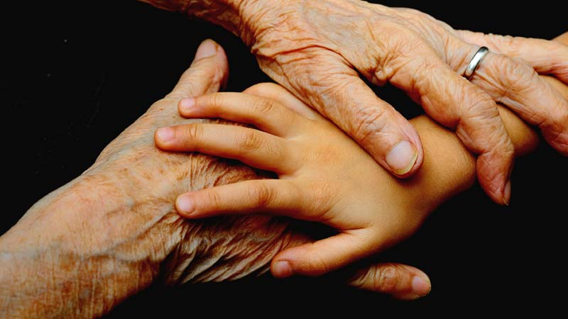 People's hands of different ages intertwine
