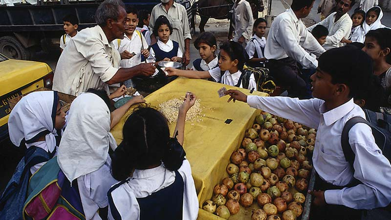 Pakistani school children buying apples
