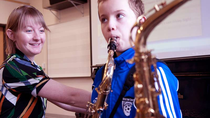 A young student learning to play the saxaphone