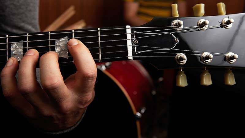 A close up of a person playing the guitar