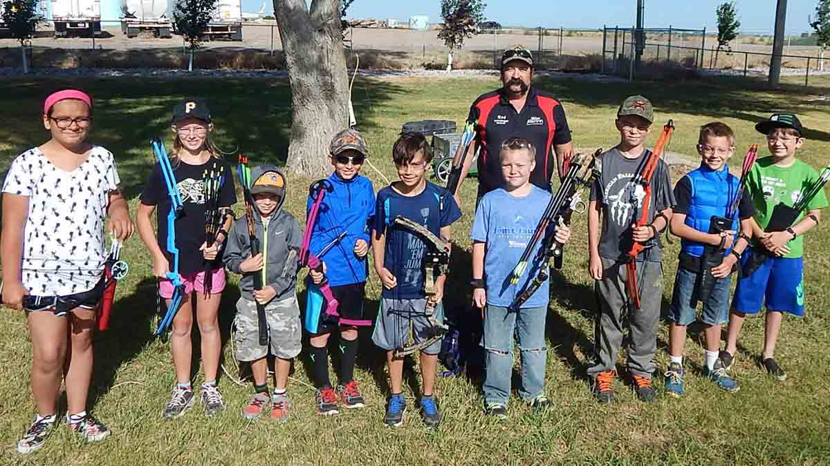 a group of kids with archery equipment