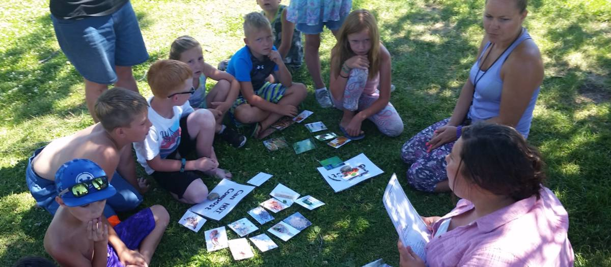 Half a dozen kids and a few adults sit in a circle around cards about composting.