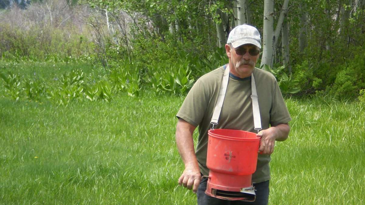 A man stands outside while wearing a t-shirt and baseball cap. A bucket hangs from a strap around his neck while he holds a crank in the bucket.