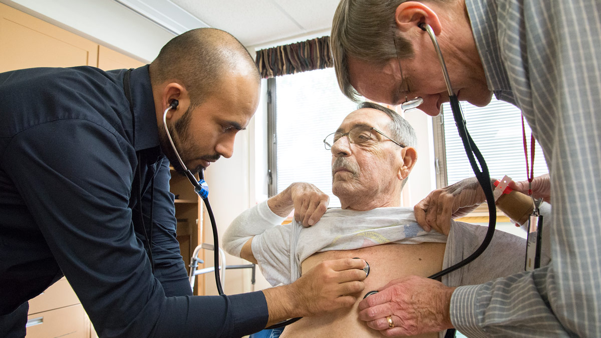 Two doctors listen to the heartbeat of a patient.