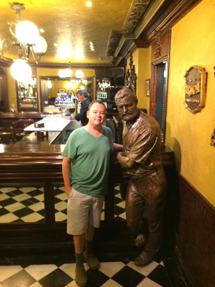 Brandon Schrand in Pamplona standing next to a statue of Ernest Hemingway