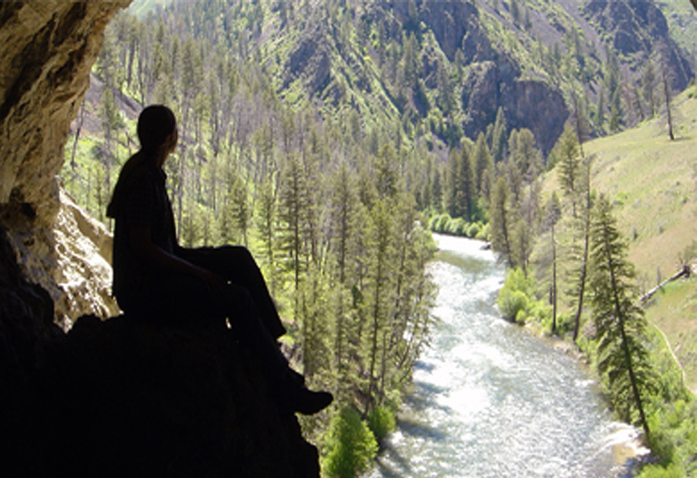 Student sitting on a rock looking over the river at Taylor Ranch