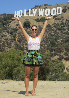 "Alecia Weaver standing under the ""Hollywood"" sign"
