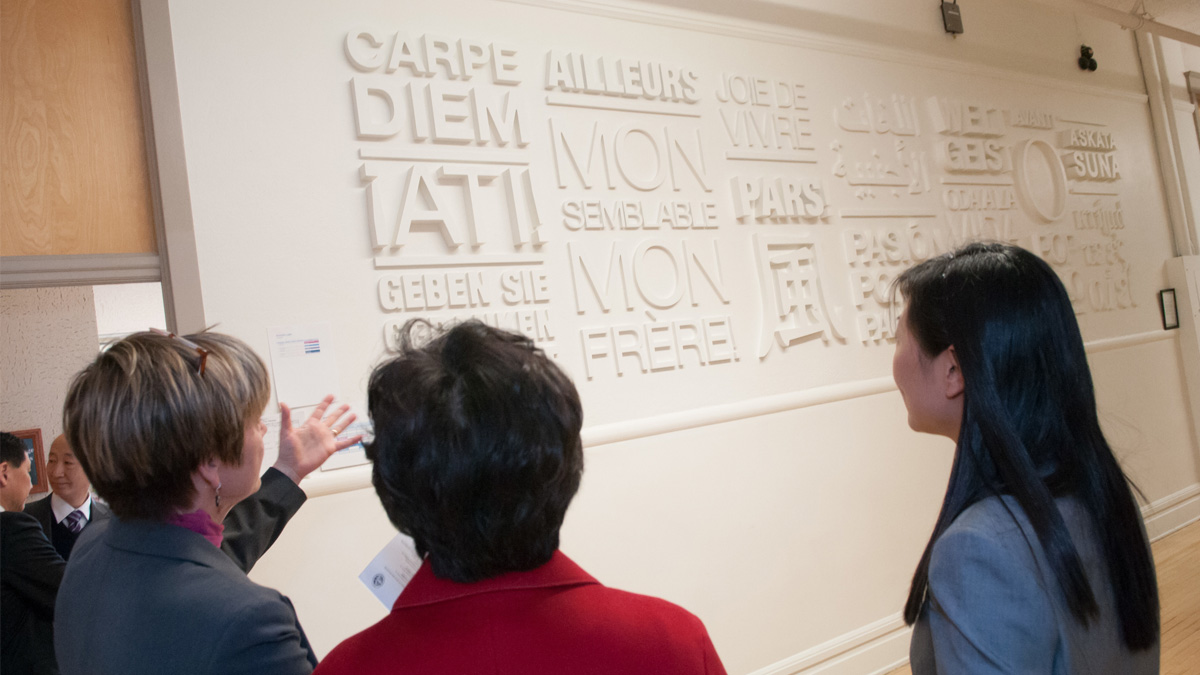 Sarah Nelson showing the wall of foreign phrases and words outside the Modern Languages and Cultures offices.