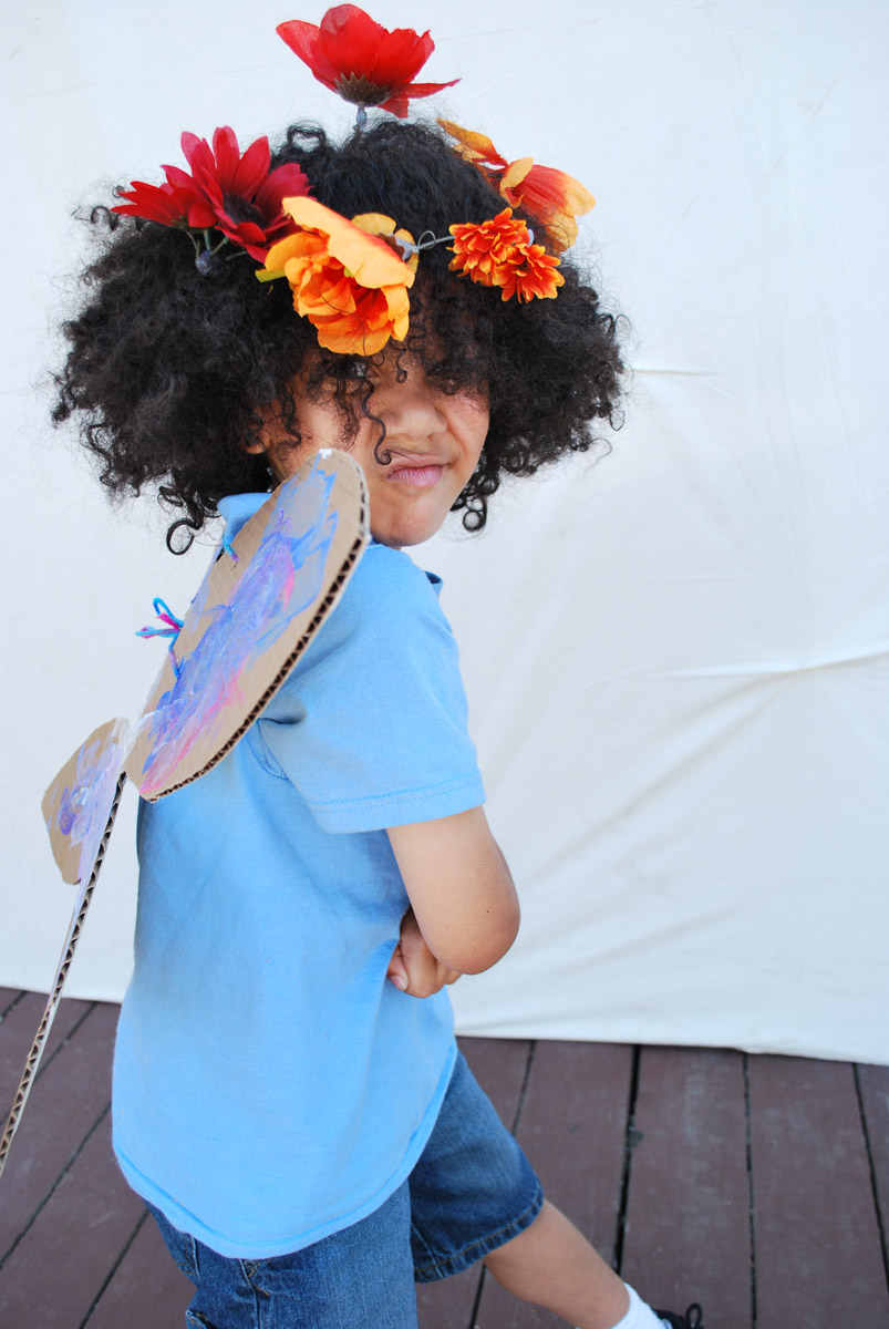 A child in costume with cardboard wings and flowers in his hair.