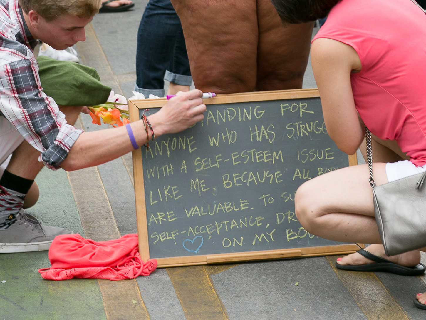 "Two people crouch by the chalkboard sign, which says, ""I am standing for anyone who has struggled with a self-esteem issue like me, because all bodies are valuable. To support self-acceptance, draw a heart on my body."""