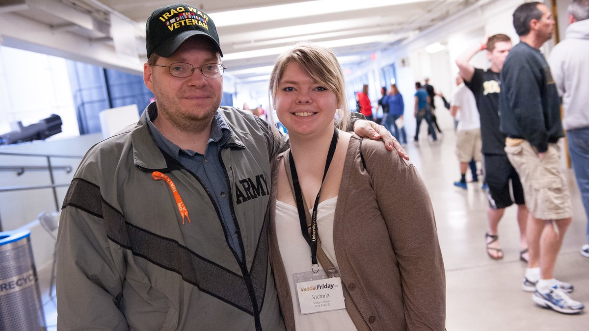 A UI student stands proudly with her father, a veteran, during the dads' weekend celebration.