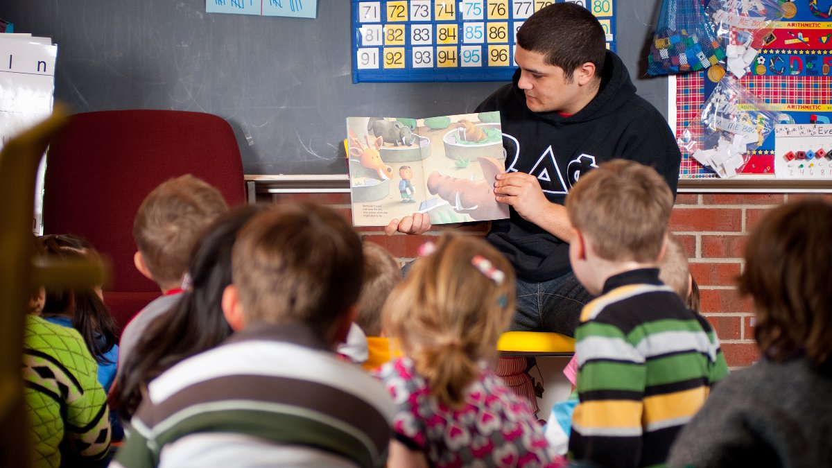 Education student reads a story to a group of young students.